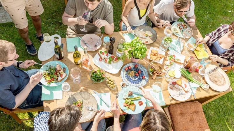 Acht Freunde beim gemütlichen Grillen und Essen an einem hellen Holztisch im Garten, Blick von oben