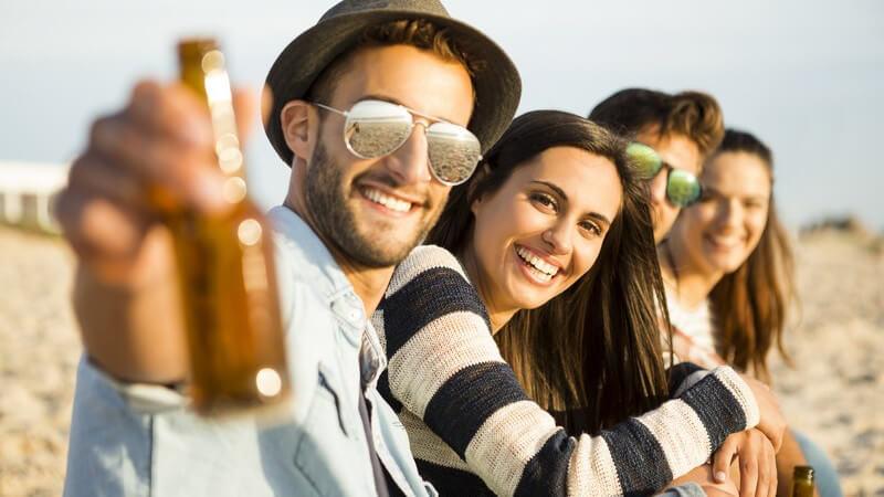Vier Freunde sitzen mit Flaschen in der Hand am Strand und lächeln in die Kamera