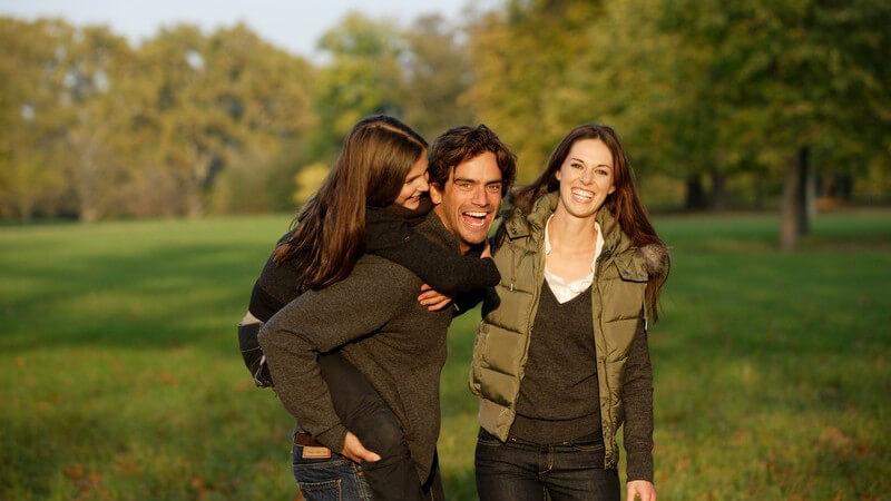 Junge lachende Familie draußen, Vater trägt Tochter auf Rücken