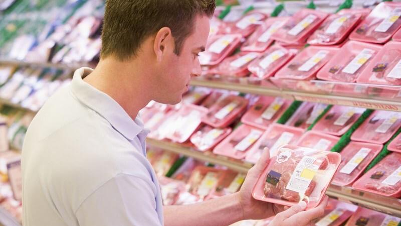 Junger Mann am Fleischregal im Supermarkt