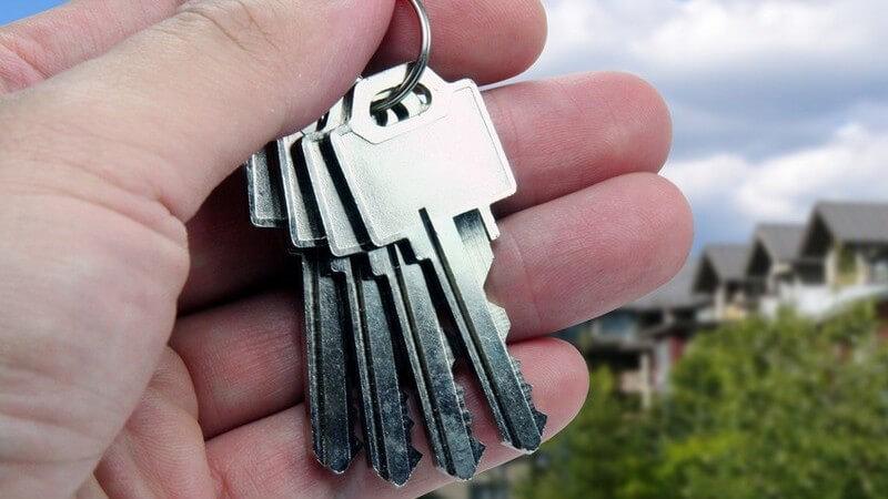 Linke Hand eines Mannes hält Haustürschlüssel; Himmel, Bäume und mehrere Einfamilienhäuser im Hintergrund