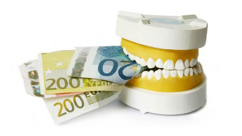 Zahnmodell beißt auf Geldscheine, weißer Hintergrund