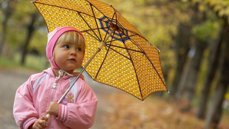 Kleines Mädchen in rosaner Kleidung mit gelbem Regenschirm im Herbst