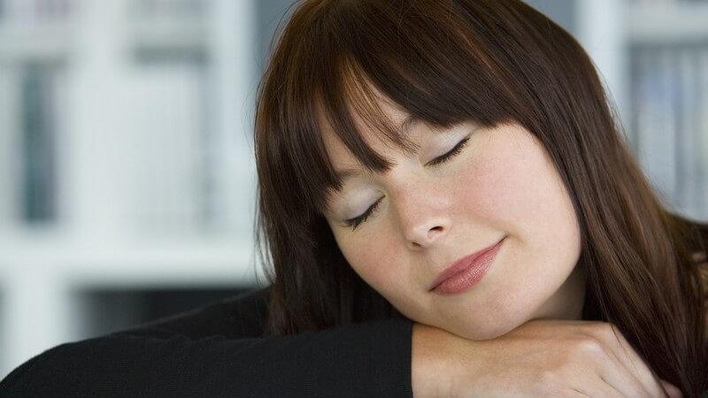 Dunkelhaarige Frau mit geschlossenen Augen lehnt ihren Kopf entspannt auf den Arm