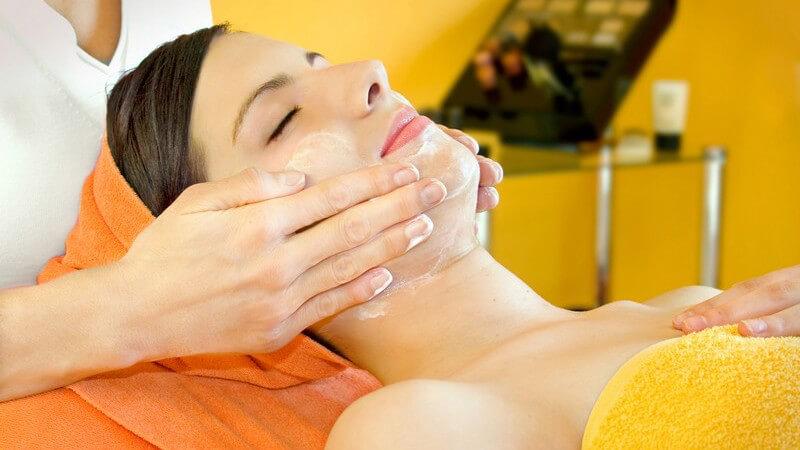 Kosmetikerin trägt einer jungen Frau mit orangem und gelbem Handtuch eine Creme auf