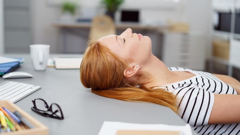 Rotblonde Frau liegt mit der Kopfrückseite auf dem Schreibtisch im Büro und schläft