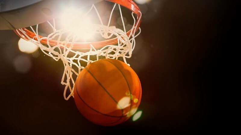 Ein Basketball im Flutlicht beim Verlassen eines Basketballkorbs (Treffer)