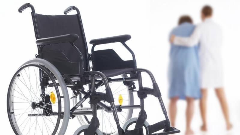 Rollstuhl, im Hintergrund hilft Ärztin einer Patientin beim Gehen