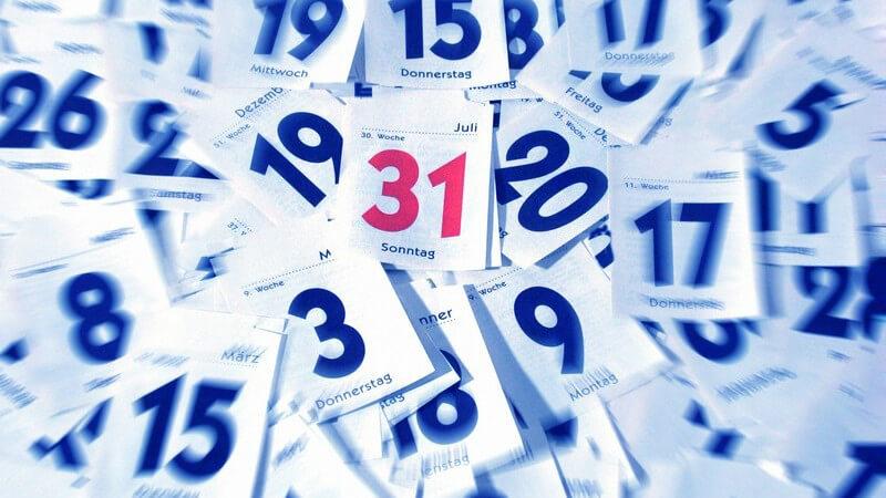 Blätter eines kleinen Abrisskalenders mit blauen Zahlen, in Mitte rote 31