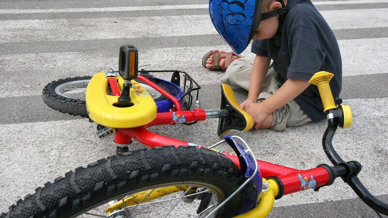 Kind ist mit dem Fahrrad gestürzt und fasst sich ans Knie