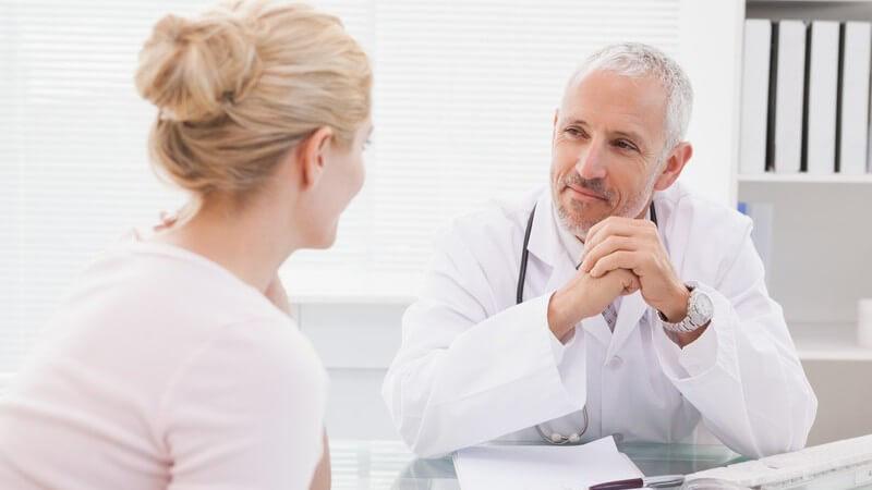 Blonde Frau mit Dutt in der Sprechstunde mit einem zufriedenen Arzt
