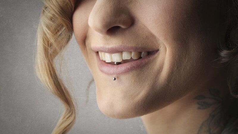 Portrait einer lächelnden Frau mit Labret-Piercing und Lockensträhne