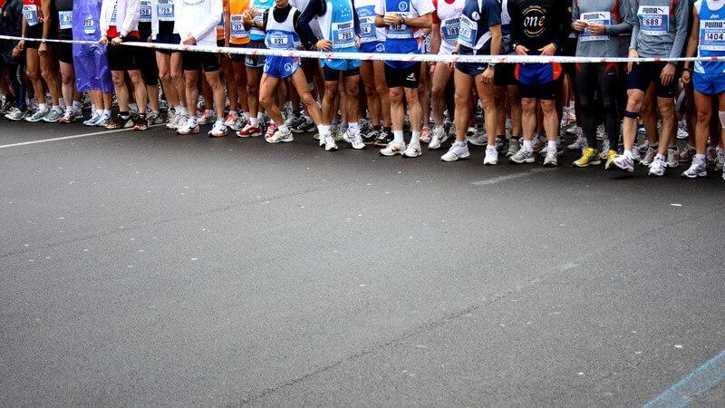 Viele Sportler stehen hinter einer Abgrenzung vor dem Marathon Start
