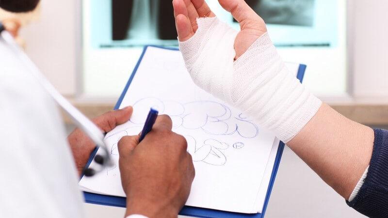 Bandagierte Hand mit Verband, im Hintergrund Röntgenbilder