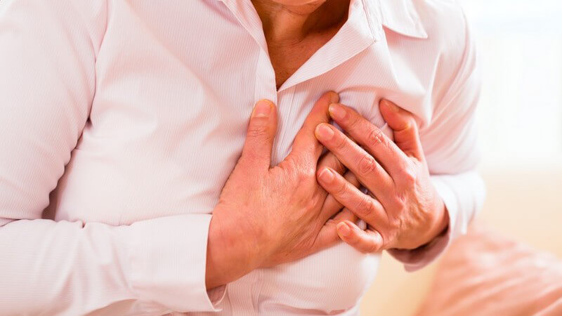 Herzinfarkt: Oberkörper einer Frau mit Brustschmerzen, sie fasst sich aufs Herz