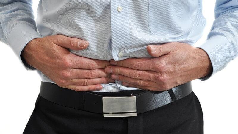 Ausschnitt Männerkörper, er drückt sich mit Händen an den Bauch, Bauchschmerzen