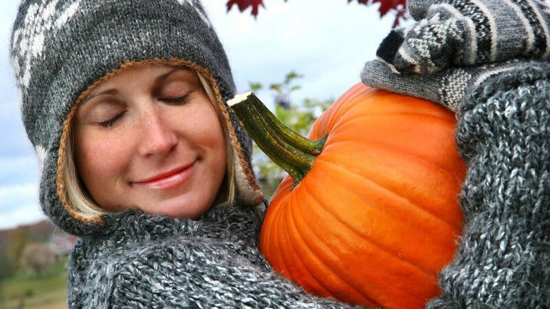 Frau mit Wollpulli, Mütze, Handschuhen umarmt Kürbis