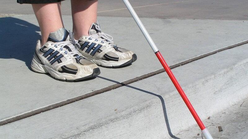 Füße eines Blinden mit Blindenstock an Straße