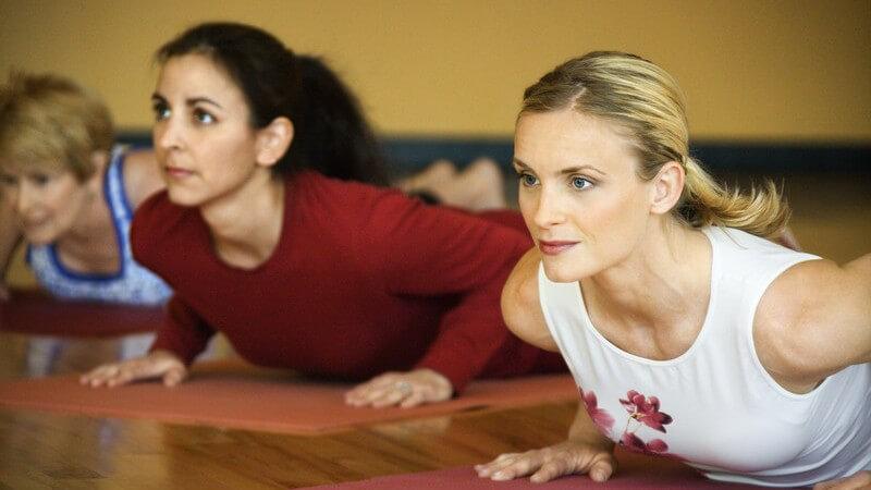 Blonde und dahinter brünette Frau stützen sich auf Yogamatten hoch