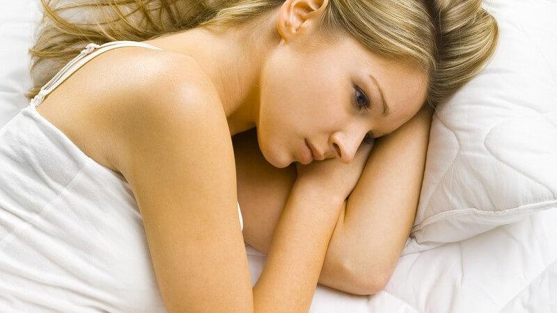 Junge blonde Frau liegt traurig auf der Seite alleine im Bett