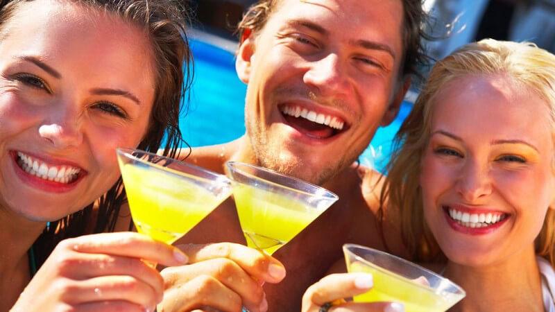 Drei Freunde am Pool mit Cocktail in der Hand