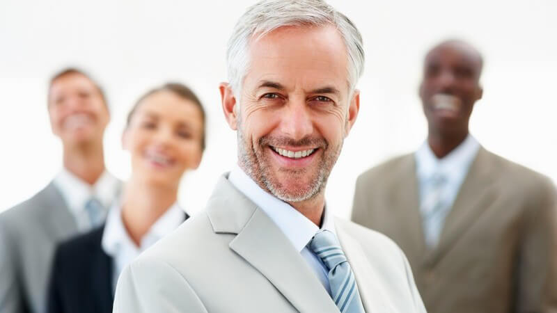 Älterer Geschäftsmann mit Kollegen im Hintergrund lacht in Kamera