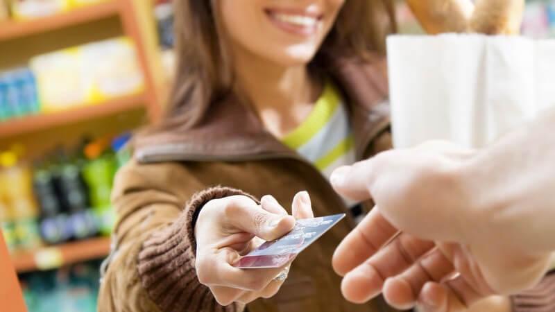 Junge Frau mit Einkaufstüte steht an Kasse und hält Kassierer Geldkarte hin