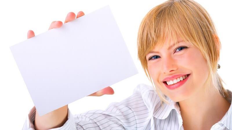 Blonde, lächelnde Frau hält leeren, weißen Briefumschlag in Kamera