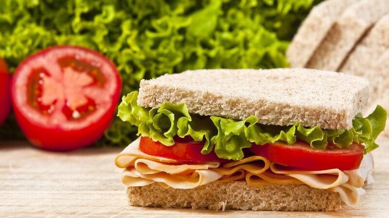 Sandwich mit Blattsalat, Tomate und Wurst - im Hintergrund Tomate, Salat und Brot