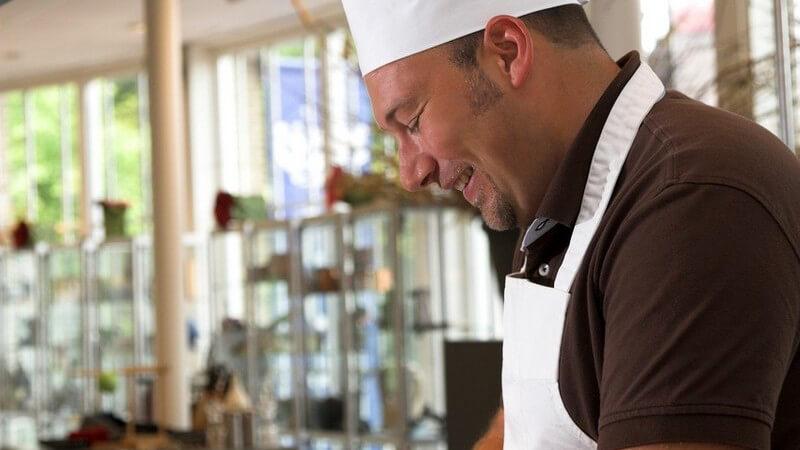 Kochen - Mann mit weißer Kochmütze und Schürze