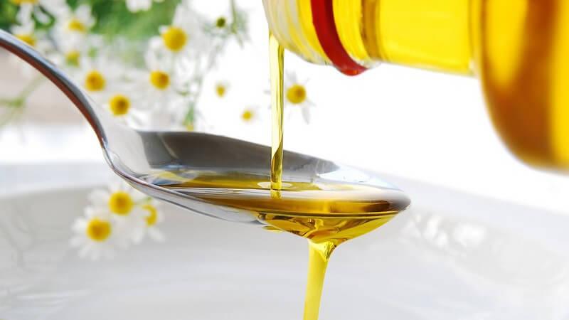 Öl wird aus Flasche auf Löffel gekippt und läuft dann in eine Schale