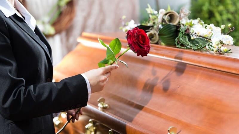 Frau in Schwarz legt bei einer Beerdigung eine rote Rose auf einen Holzsarg