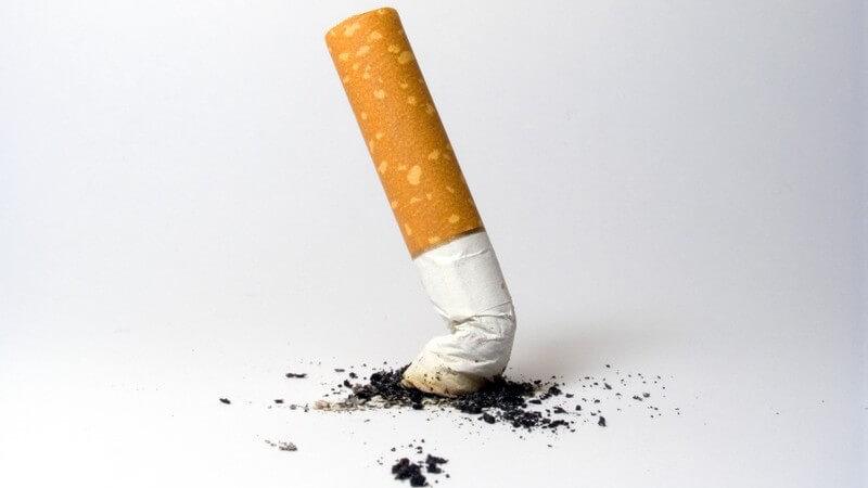 Zigarettenstummel, der ausgedrückt wurde, schwarze Krümel darum