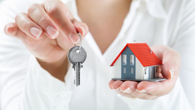 Frau in weißer Bluse hält zwei Schlüssel hoch, in der anderen Hand ein Hausmodell