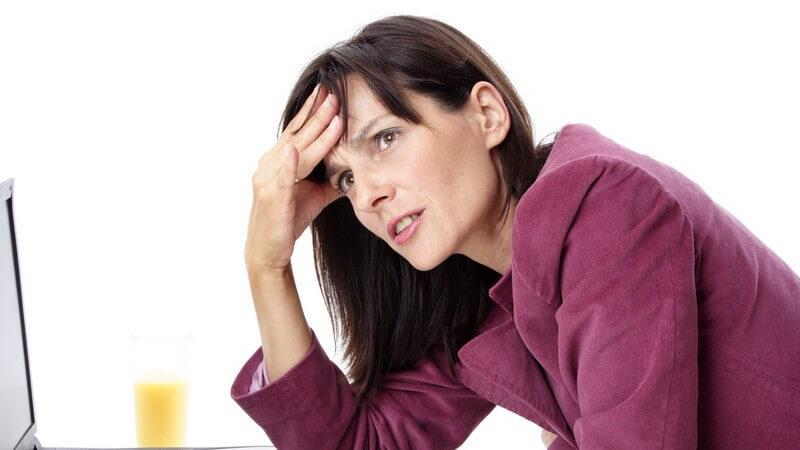 Dunkelhaarige Frau vor ihrem Laptop fasst sich mit besorgtem Blick an die Stirn