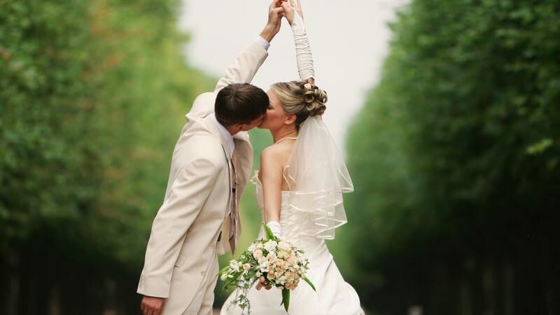 Küssendes Brautpaar, im Hintergrund schöne Landschaft