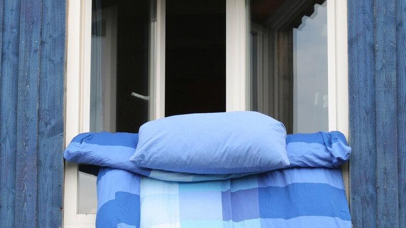 Bettwäsche hängt zum Lüften aus Fenster eines blauen Hauses