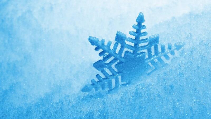 Grafik blaue Schneeflocke im Schnee