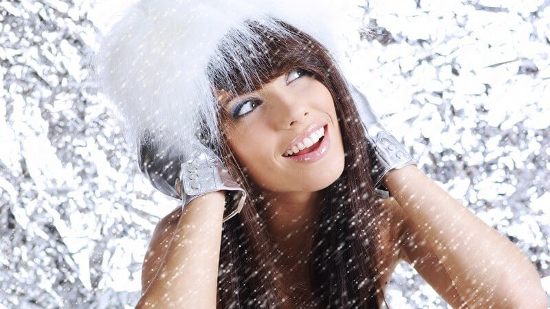Lachende Frau mit Fellmütze, grafischer Schnee Hintergrund