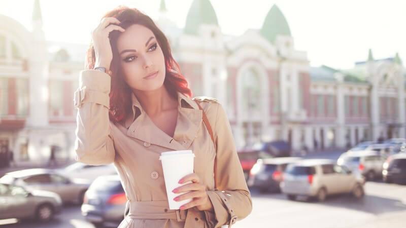 Junge Frau in beigem Mantel steht in der Morgensonne an einem Parkplatz und hält einen Kaffee in der Hand