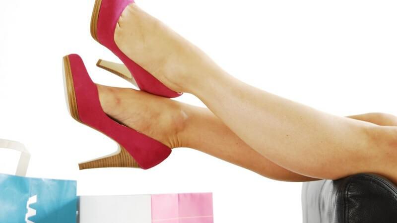 Frauenbeine mit roten Stöckelschuhen über Sessel gelehnt, im Hintergrund Einkaufstüten