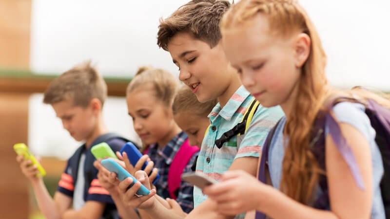 Fünf junge Schüler mit Schulrucksack befassen sich alle mit ihrem Smartphone
