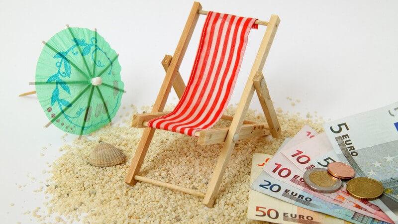 Mini-Sonnenliege auf Sand, daneben Gelscheine - Urlaubsgeld