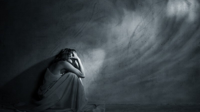 Schwarz-weiß Bild Frau hockt im dunklem leeren Zimmer an kahler Wand Depression Borderline Trauer