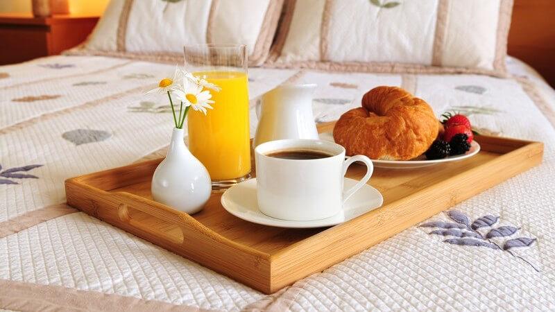 Frühstückstablett für Frühstück im Bett mit Kaffee, Orangensaft, Croissant und Früchten auf Ehebett