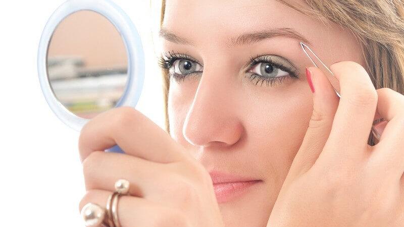 Junge Frau schaut in Handspiegel und zupft sich die Augenbrauen