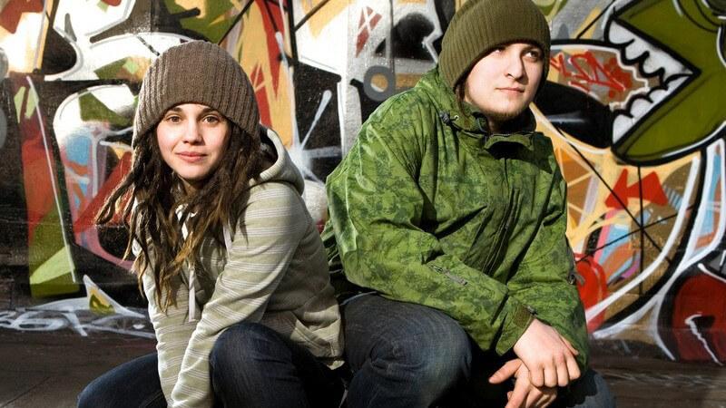 Junge und Mädchen im Hip Hop Style hocken vor Graffiti Wand