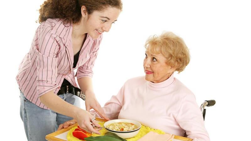 Junge Frau bringt alter im Rollstuhl sitzender Dame Tablett mit Essen
