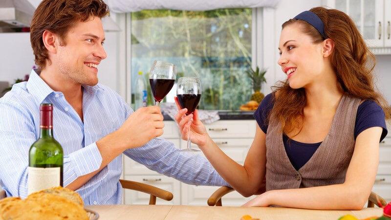Junges Paar sitzt am Küchentisch und stößt mit Rotwein an