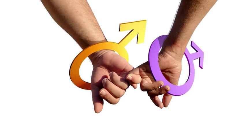 Die Hände zweier schwuler Männer mit dem Marszeichen am Handgelenk